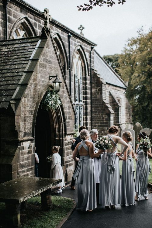 Bridal party in grey multiway bridesmaid dresses outside the church