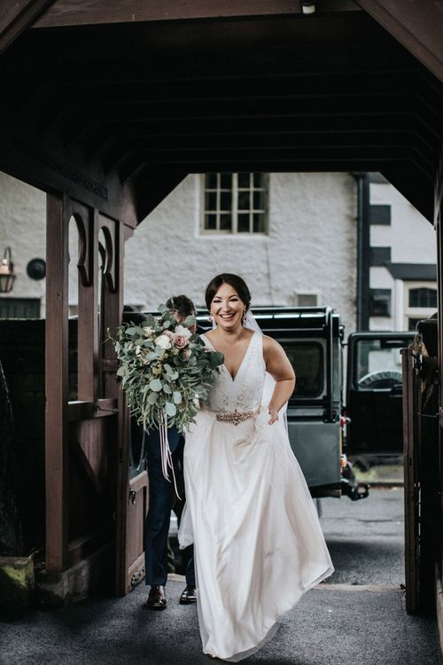 Smiling bride in blush pink wedding dress arriving at the church wedding ceremony