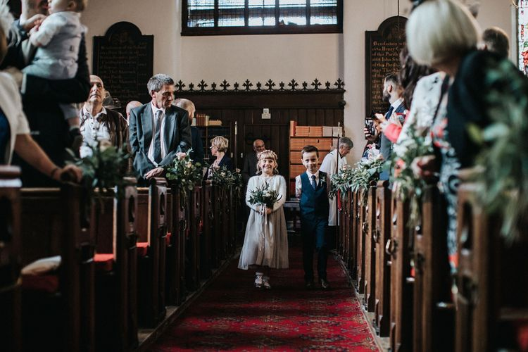 Flower girl and page boy walking down the aisle at the church wedding ceremony