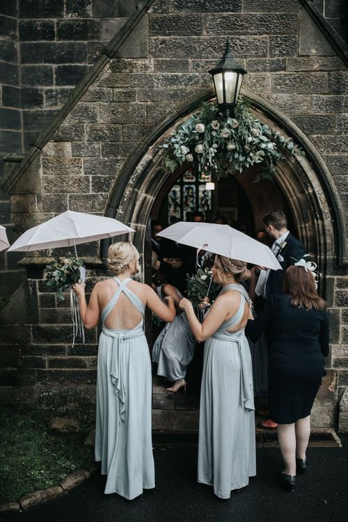 Bridal party standing outside the church in grey multiway bridesmaid dresses