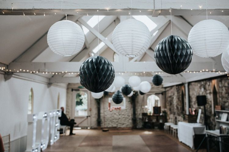 Grey and white hanging paper lanterns and honey comb balls