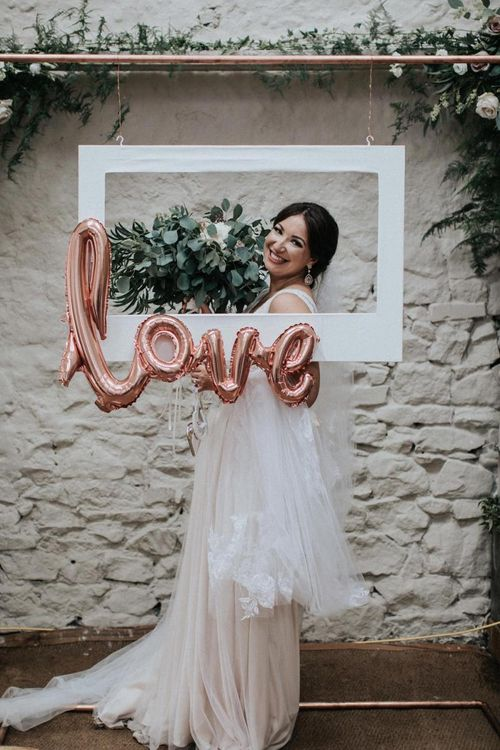Bride posing at Selfie station with foil ballon and white frame