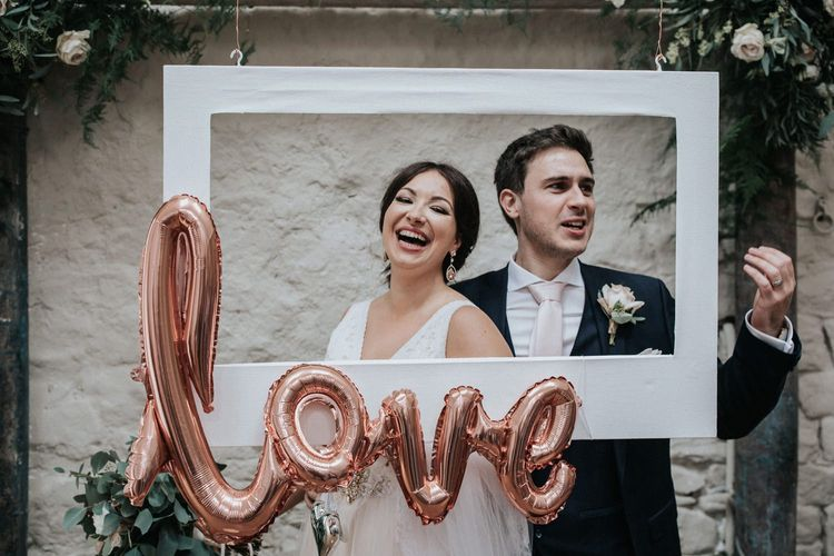 Bride and groom posing at Selfie Station with white frame and gold foil balloon.