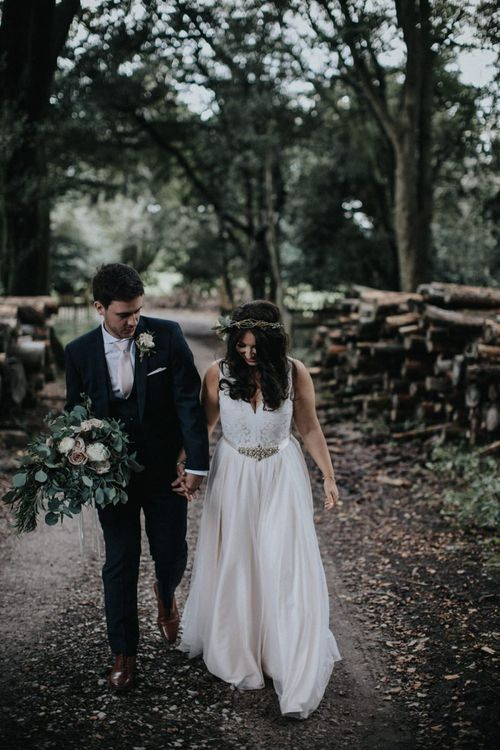 Boho bride in blush wedding dress and flower crown with groom holding her bouquet