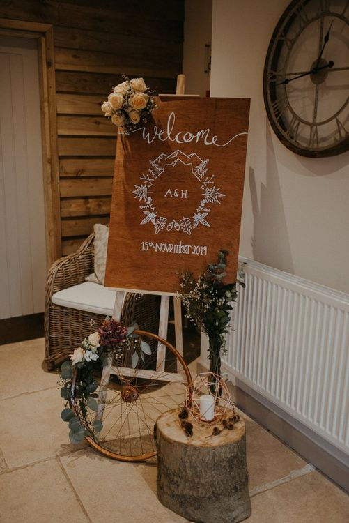 Wooden wedding welcome sign and rustic decor at Lapstone Barn