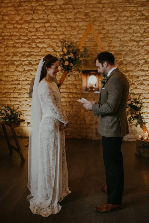 Bride and groom exchanging vows at barn wedding ceremony