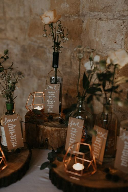 Rustic table plan with tree slices, bottles and terrariums