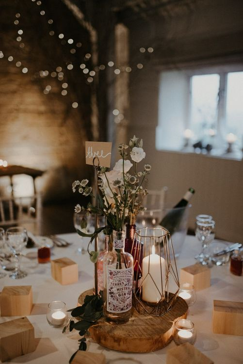 Rustic centrepiece decor with tree slice, terrarium, gin bottles and flowers
