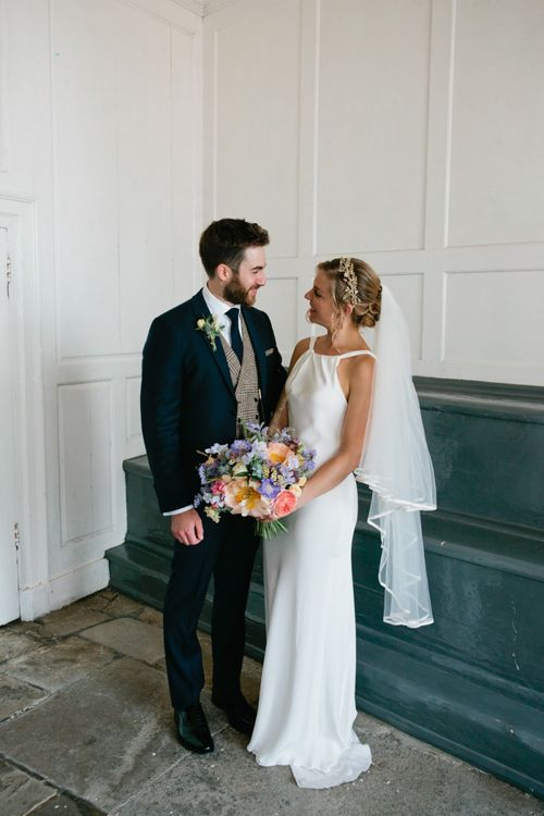 Bride in Minimal Halter Neck Wedding Dress and Groom in Traditional Suit