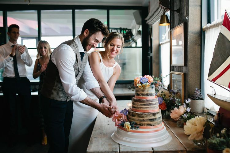 Bride and Groom Cutting the Semi Naked Wedding Cake Decorated with Ribbon and Flowers