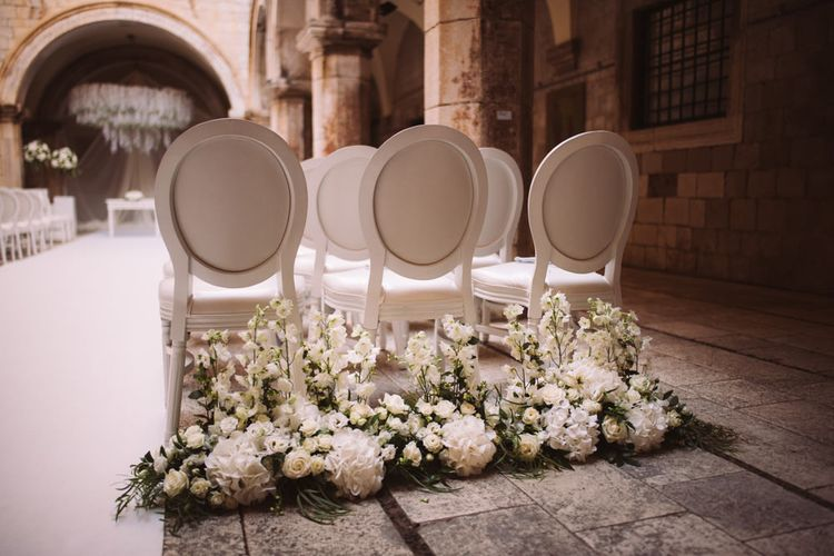 White Wedding Ceremony Chairs with White Floral Arrangement