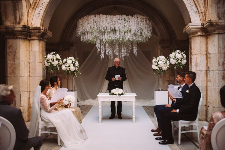 Wedding Party Sitting at the Altar during Wedding Ceremony at 16 Century Palace in Croatia