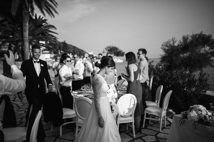 Black and White Portrait of Bride and Groom Entering the Outdoor Wedding Reception