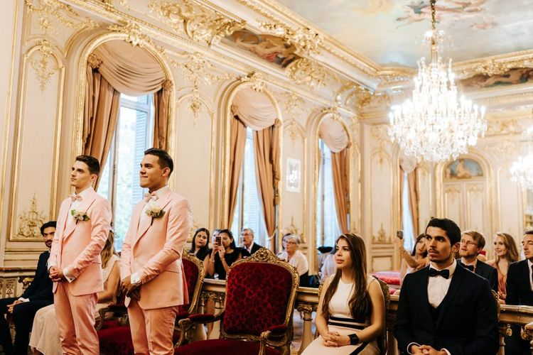 Grooms wearing pink wedding suits in ornate and golden ceremony room in Paris city hall