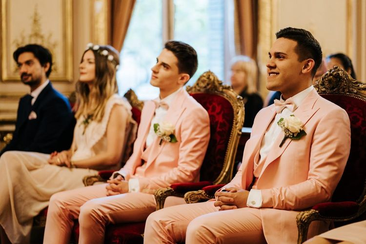 Grooms at intimate ceremony in Paris wearing pink wedding suits