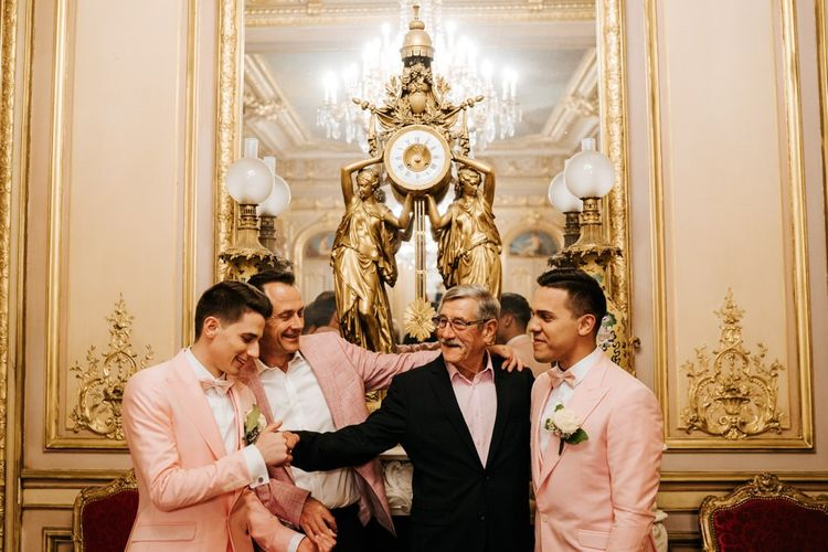 Grooms and relatives enjoy a moment at intimate ceremony with gold and ornate styling