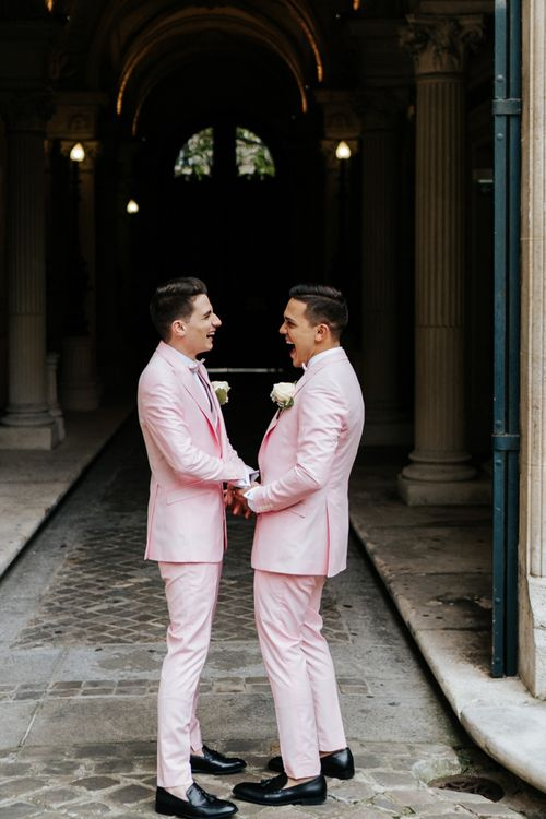 Two grooms in pink wedding suits do first look at Paris ceremony