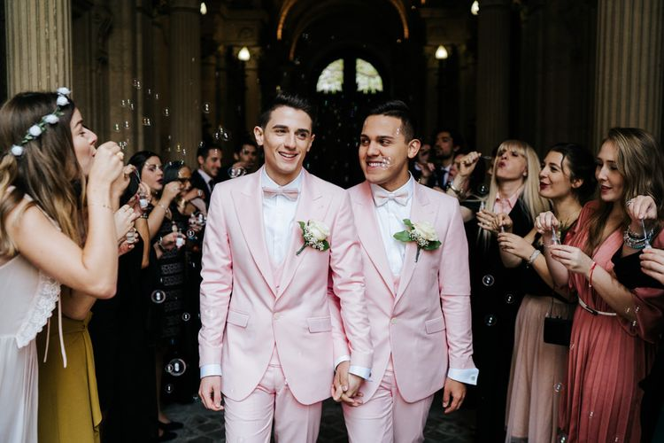 Grooms wearing pink wedding suits walk through a bubble tunnel at Paris same sex wedding