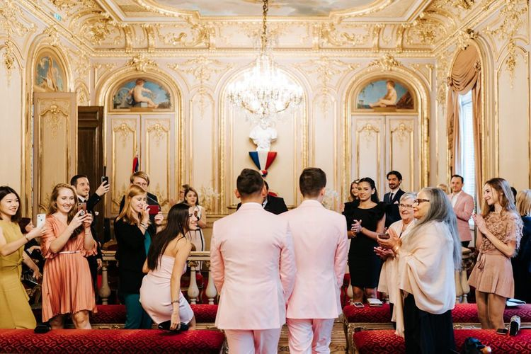 Grooms wearing pink wedding suits walk down the aisle together at beautiful ceremony in Paris city hall