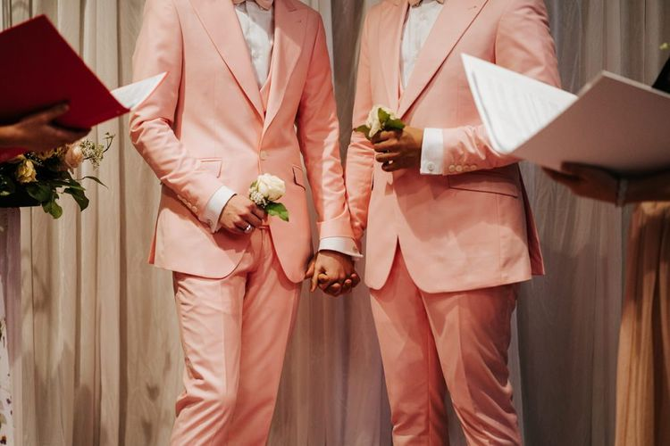 Grooms holding hands as two of their closest friends officiate the second ceremony