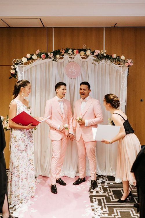 Grooms wearing pink wedding suits with personalised aisle arch decor at second Paris intimate ceremony