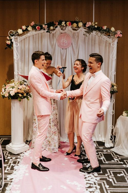 Both grooms wearing pink wedding suits and their best friends smile at Paris same sex wedding
