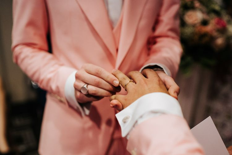 Grooms placing the wedding bands on each others finger