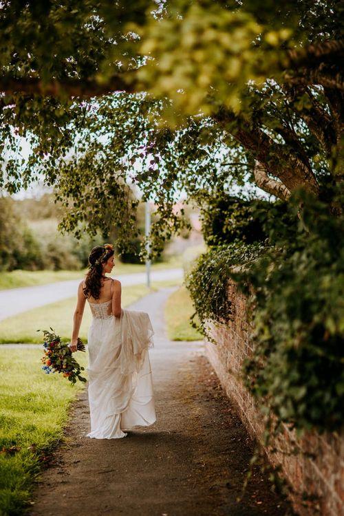 Bride Walking Down the Lane Holding Up Her Sottero & Midgley Wedding Dress