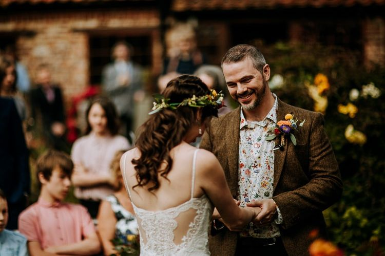 Groom in Wool Blazer and Floral Shirt Holding his Brides Hands During the Wedding Ceremony