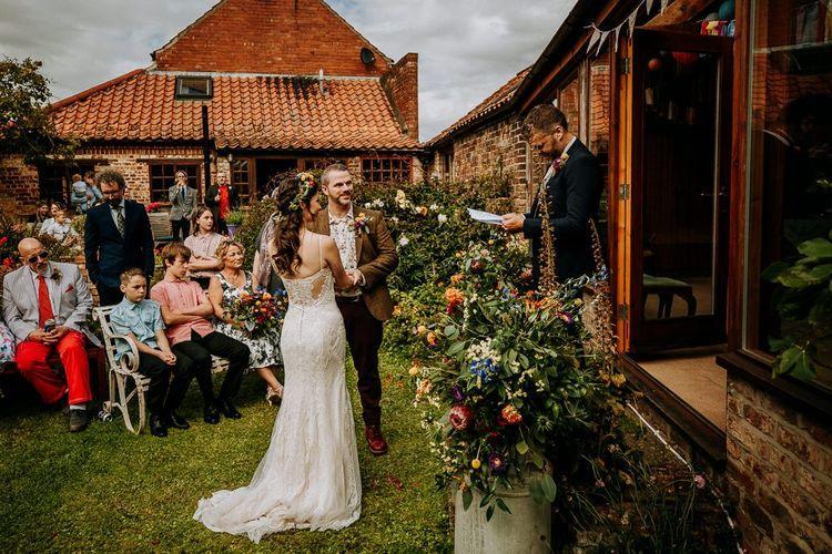 Outdoor Garden Wedding Ceremony with Milk Churn Filled with Bright Wedding Flowers