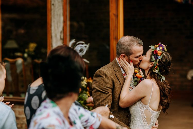 Bride in Lace Wedding Dress and Flower Crown Kissing at the Wedding Ceremony