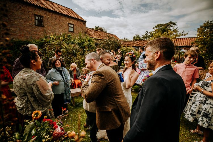 Groom in Wool Suit Being Congratulated by Wedding Guests