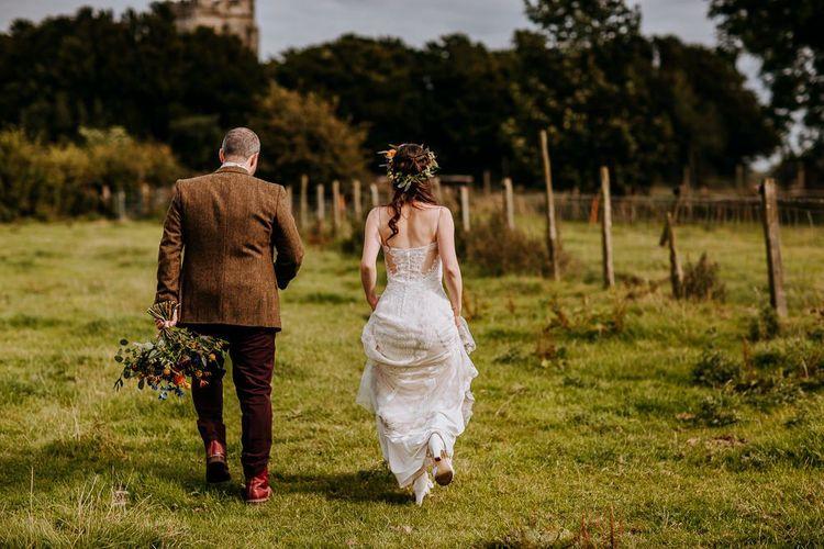 Bride in Sottero & Midgley Wedding Dress and Flower Crown and Groom in Brown Wool Suit