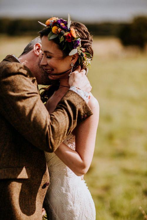 Groom in Brown Wool Suit Kissing His Bride in a Colourful Flower Crown