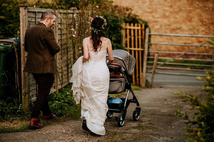 Bride in Sottero & Midgley Wedding Dress and Colourful Flower Crown and Groom in Brown Suit