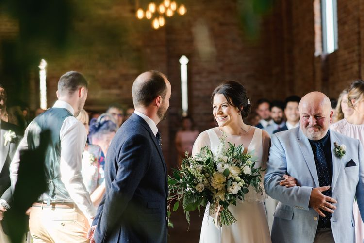 Bride greets groom at altar holding white wedding flowers bouquet