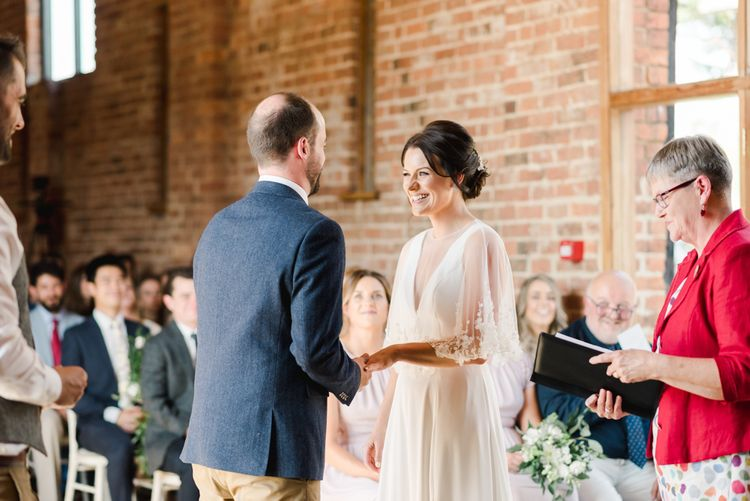 Bride in lace overlay jacket with groom during ceremony