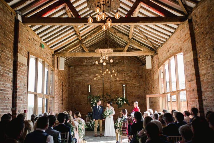 Barn wedding ceremony with white wedding flowers