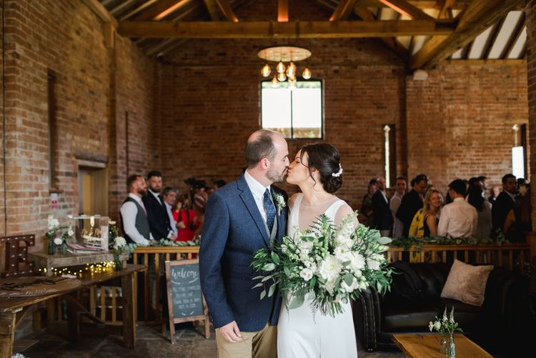 Bride and groom kiss after ceremony with white wedding flowers
