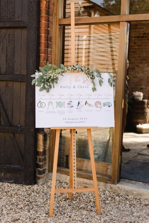 Wedding order of the day sign with icons decorated in white wedding flowers