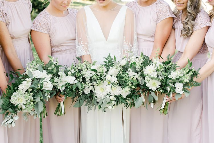 Bridesmaids in blush dresses holding white wedding flowers