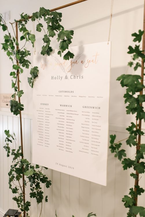 Copper piping wedding seating plan with white wedding flowers
