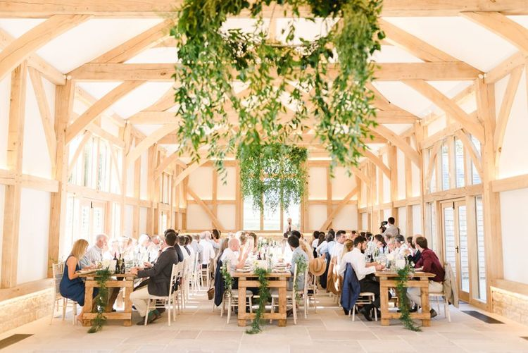 Foliage chandelier and white wedding flowers at barn reception