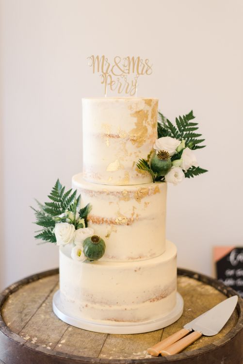 Semi-naked wedding cake with white wedding flowers and gold foil