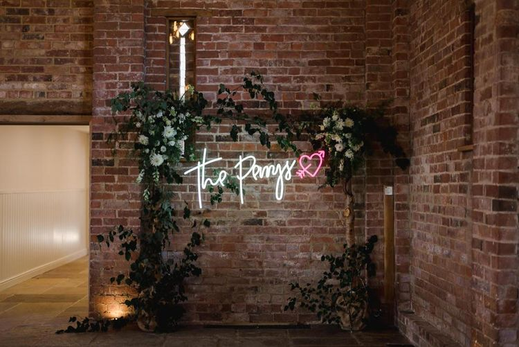 Personalised neon sign and white wedding flowers