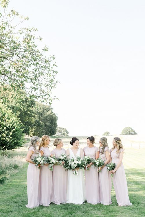 Blush bridesmaid dresses with white wedding flowers