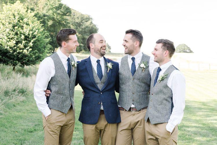 Groom in navy wedding jacket with groomsmen in matching grey waistcoats