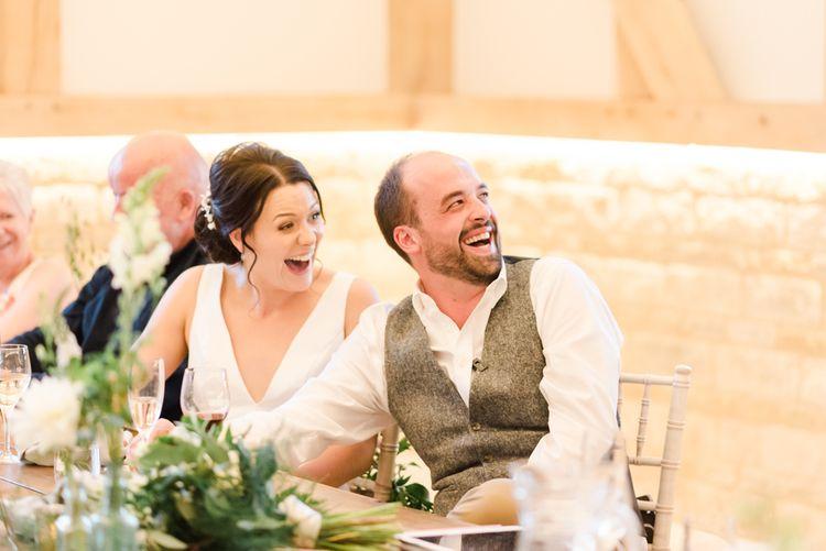 Bride and groom enjoy wedding speeches