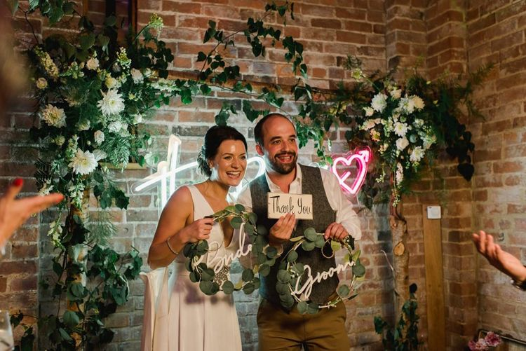 Bride and groom pose with personalised neon sign and white wedding flowers hoop decor