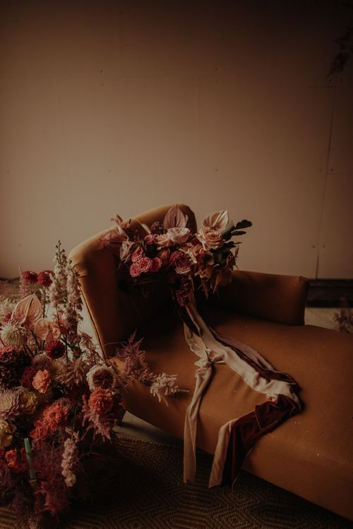Pink wedding bouquet tied with ribbon resting on a chaise lounge
